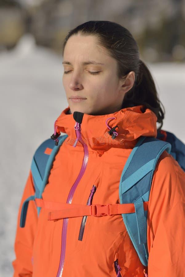 Porträt einer jungen Frau mit dem Rucksack, der in den Bergen wandert stockfotos