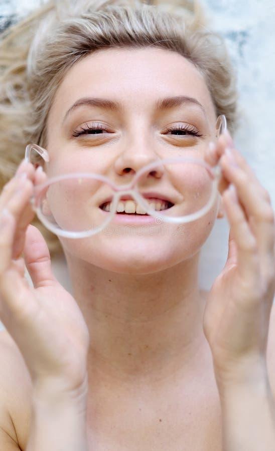 Porträt einer jungen Frau mit den Gläsern und blondem Haar, welche die Gläser vor ihrem Gesicht, ihre Gläser unscharf halten stockfoto
