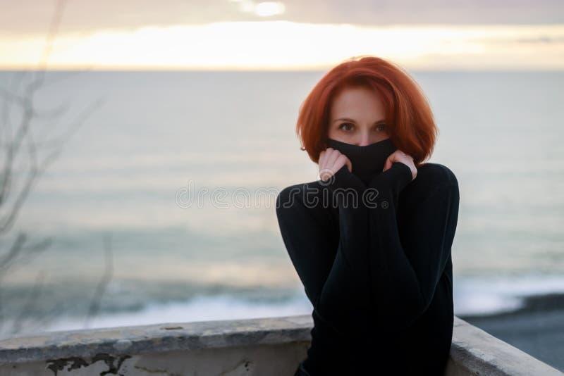 Porträt einer jungen Frau in einer schwarzen Strickjacke an einem kalten Frühlingsabend im Hintergrund des Meeres und des Sonnenu lizenzfreie stockfotografie