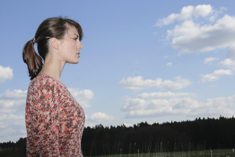 Porträt einer jungen Frau vor einem blauen Himmel lizenzfreie stockbilder