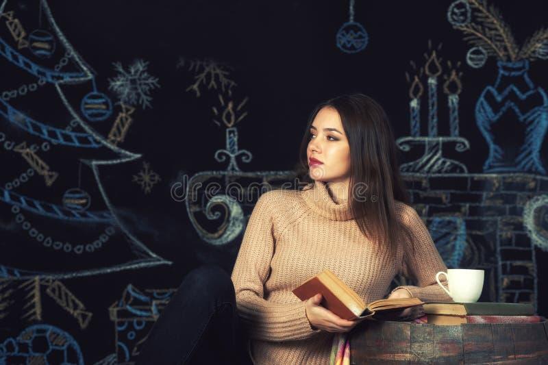 Porträt einer jungen Frau in einer warmen Strickjacke auf einem dunklen Hintergrund stockbild