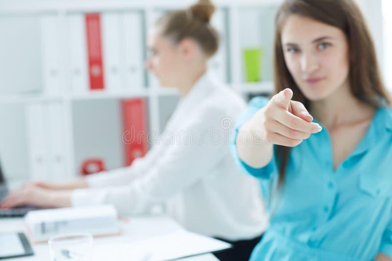 Porträt einer jungen Geschäftsfrau, die gerade auf die Kamera, mit weiblichem Kollegen auf dem Hintergrund zeigt Foto mit lizenzfreies stockbild
