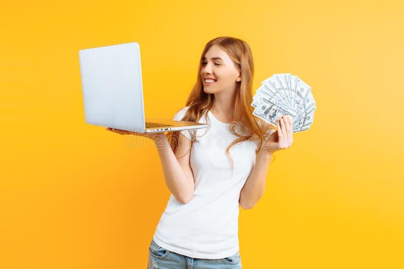 Porträt einer jungen glücklichen Frau, die, unter Verwendung eines Laptoplaptops trägt und in der Hand Geld, auf gelbem Hintergru stockfoto