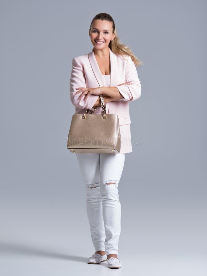 Porträt einer jungen glücklichen Frau mit Handtasche stockfoto