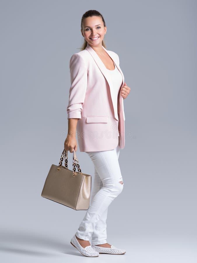 Porträt einer jungen glücklichen Frau mit Handtasche stockfotos