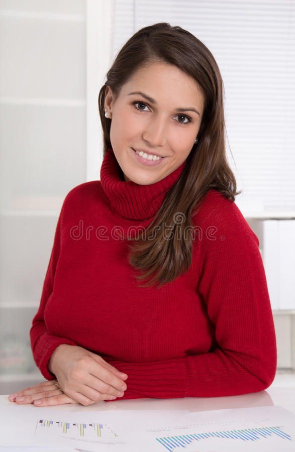 Porträt einer jungen hübschen Frau am Schreibtisch - Auszubildender in einem Büro stockbilder
