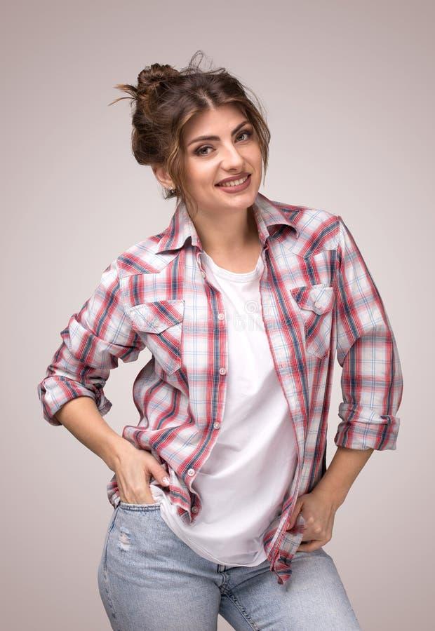 Porträt einer jungen lächelnden Frau im karierten Hemd und im weißen T-Shirt, stehend mit den Armen in den Taschen stockbilder