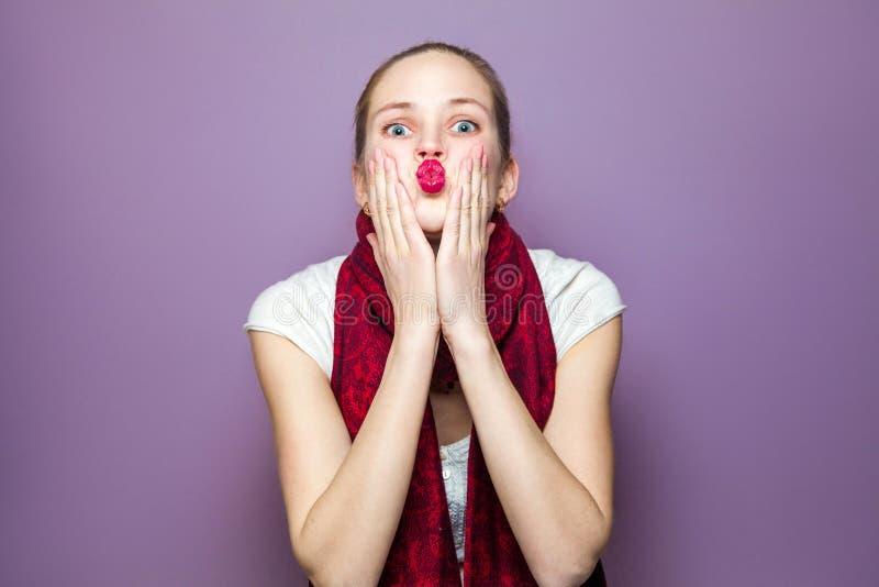 Porträt einer jungen netten Frau mit rotem Schal und Sommersprossen auf ihrem Schlagkuß und dem Betrachten des Gesichtes der Kame lizenzfreies stockbild