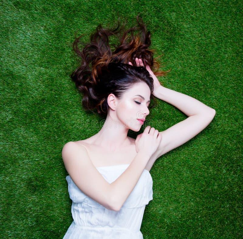 Porträt einer jungen Rothaarigefrau, die sich auf grünem Frühling gra hinlegt stockfoto