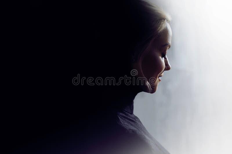 Porträt einer jungen ruhigen Frau im Profil Konzept der inneren Welt und der Psychologie, die Dunkelheit und Lichtseite der Persö lizenzfreies stockbild