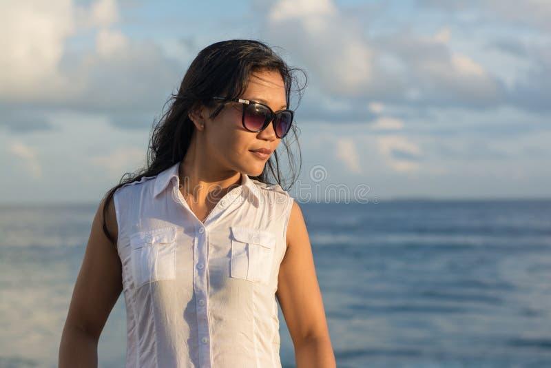 Porträt einer jungen schönen asiatischen Dame in der Sonnenbrille, die eine Seite schaut lizenzfreie stockbilder
