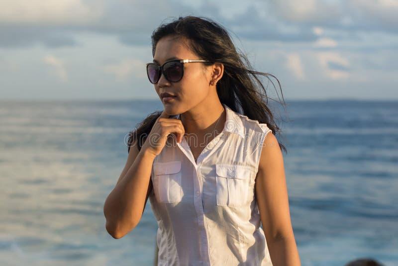 Porträt einer jungen schönen asiatischen Frau in der Sonnenbrille, die eine Seite schaut lizenzfreies stockfoto