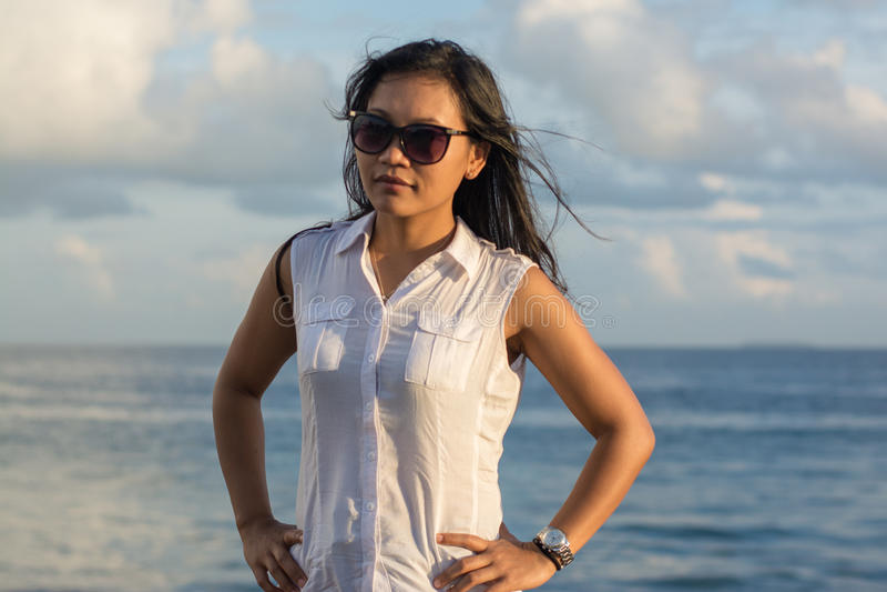 Porträt einer jungen schönen asiatischen Frau in der Sonnenbrille mit Ozean am Hintergrund stockbilder