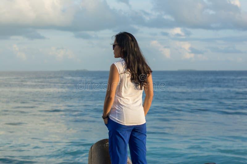 Porträt einer jungen schönen asiatischen Frau, die nahe Ozean denkt stockbilder