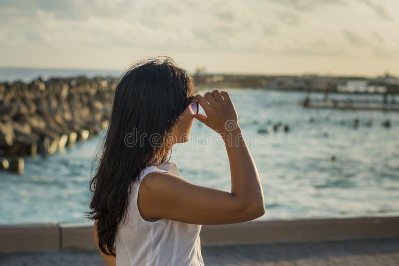 Porträt einer jungen schönen asiatischen Frau, die Ozean auf dem Stadtstrand während der Sonnenuntergangzeit betrachtet stockfotografie
