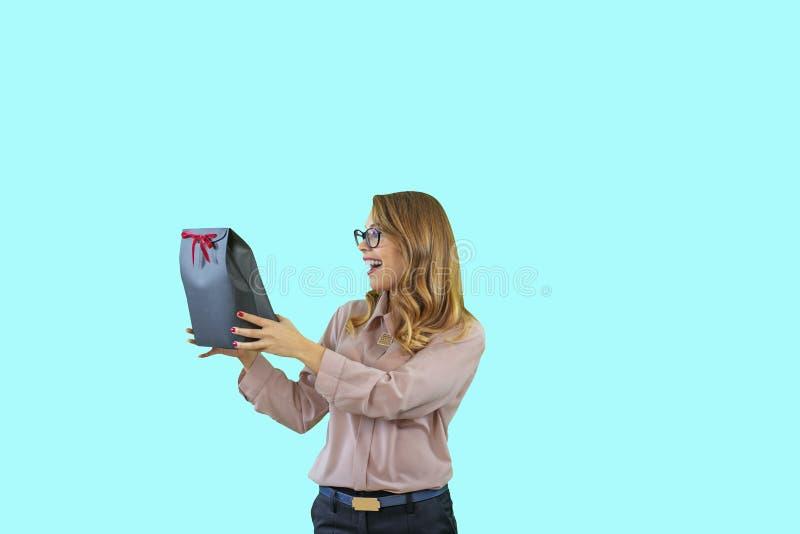 Porträt einer jungen schönen Blondine in den Gläsern, die einen Kasten mit einem roten Samtband auf ihren ausgestreckten Händen h stockfotografie
