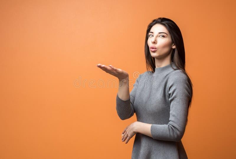 Porträt einer jungen schönen Geschäftsfrau im neutralen Kleid, das heraus leere Hand hält und Kamera untersucht lizenzfreie stockfotografie