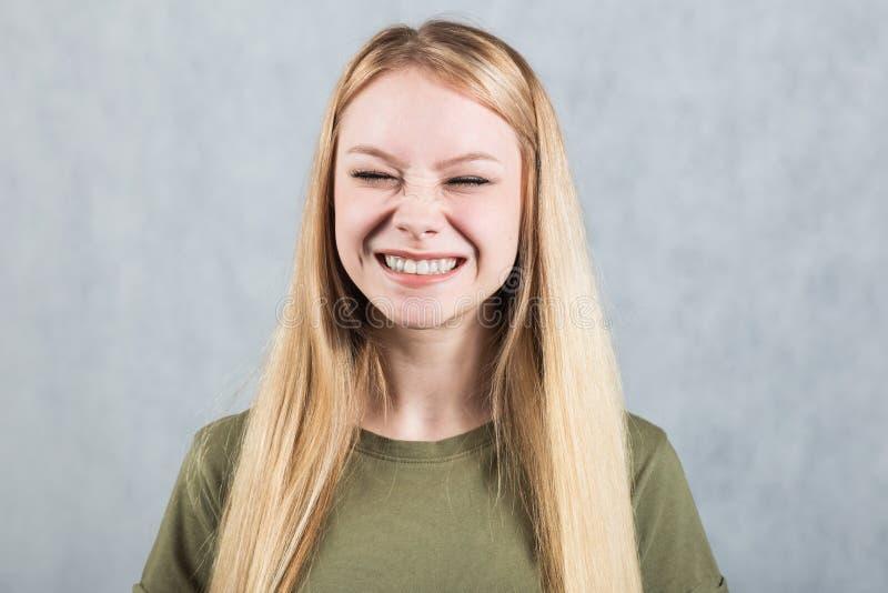 Porträt einer jungen schönen lachenden Frau auf einem grauen Hintergrund stockbilder