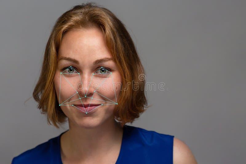 Portr?t einer jungen sch?nen roten Haarfrau auf einem grauen Hintergrund Biometrische ?berpr?fung, Gesichtskonzept stockfotos