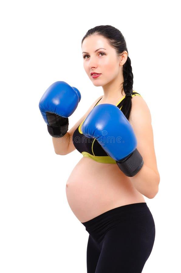 Porträt einer jungen schönen schwangeren Frau mit Boxhandschuhen stockfoto