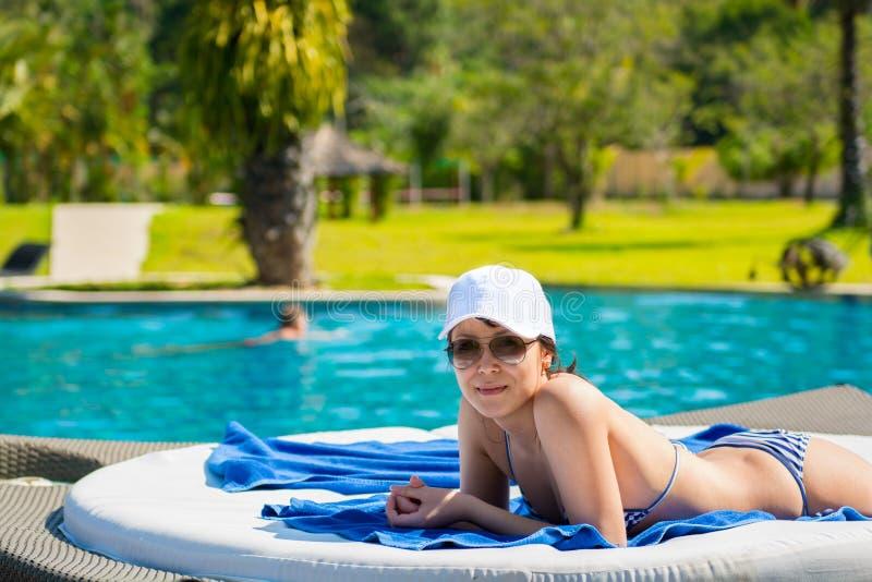Porträt einer jungen Schönheit in der weißen Kappe und in der Sonnenbrille stockfoto