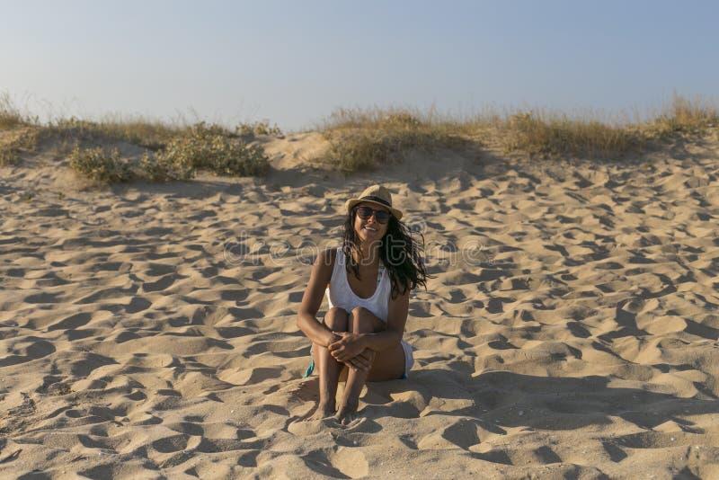 Porträt einer jungen Schönheit, die am Strand bei Sonnenuntergang sitzt Sommer, Spaß und Lebensstil lizenzfreies stockbild