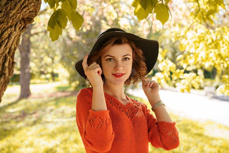 Porträt einer jungen Schönheit in einem Hut an einem sonnigen Herbsttag stockfotografie