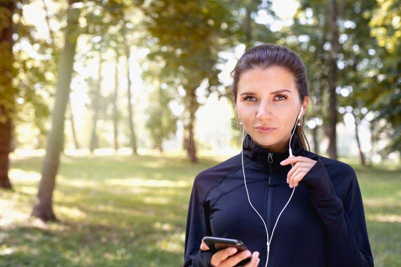 Porträt einer jungen sportlichen Brunette-Frau, die mit Kopfhörern im Park im Freien herumläuft lizenzfreies stockbild
