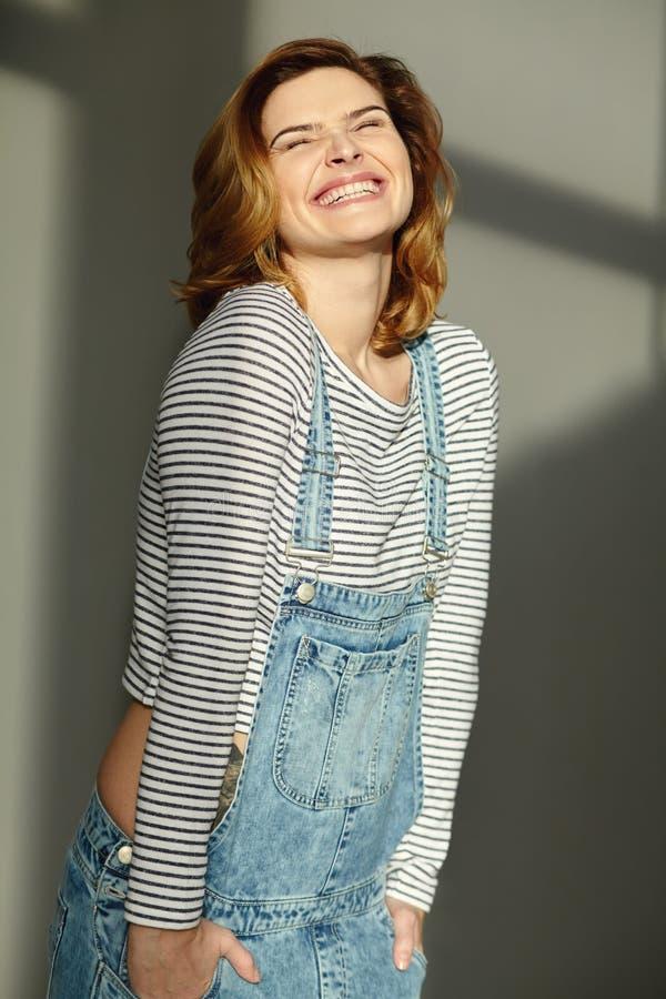 Porträt einer jungen stilvollen emotionalen lächelnden Frau im Jeansoverall lizenzfreie stockfotos