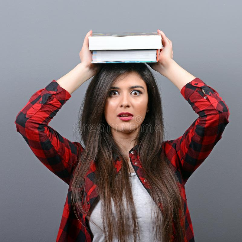Porträt einer jungen Studentenfrau, die Bücher auf Kopf gegen grauen Hintergrund hält Ermüdet vom Lernen/, das Konzept studiert lizenzfreies stockfoto