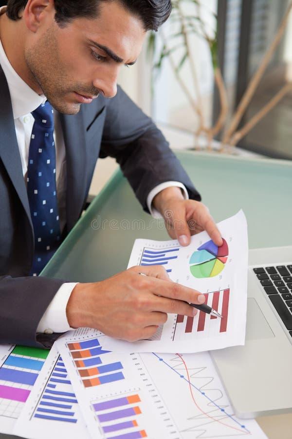 Porträt einer jungen Verkaufsperson, die Statistiken studiert stockbilder
