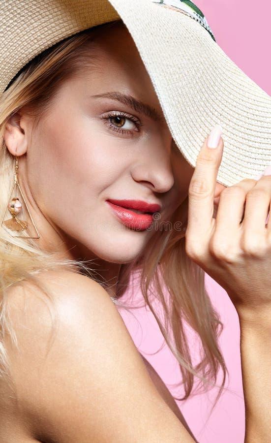 Porträt einer lächelnden attraktiven jungen Frau im Sommerhut auf rosa Hintergrund stockfotografie