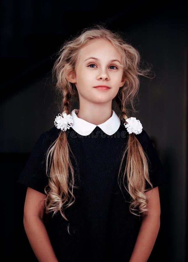 Porträt einer lächelnden Blondine Mädchen mit sieben Jährigen in der Schuluniform stockfotos