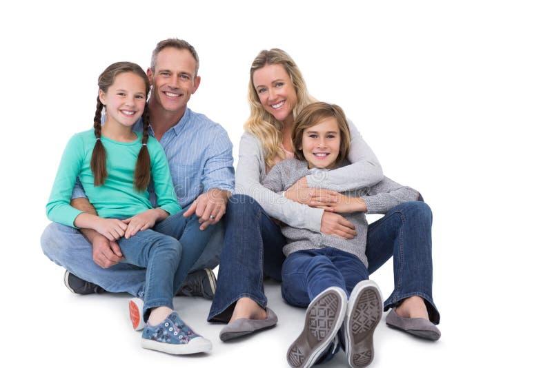 Porträt einer lächelnden Familie, die auf dem Boden sitzt stockfotografie