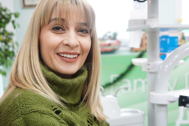 Porträt einer lächelnden Frau, die Kamera betrachtet, nachdem der Zahnarzt besucht worden ist stockfotografie