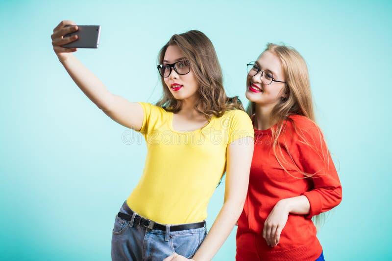 Porträt einer lächelnden Frau, die selfie Foto auf dem Smartphone lokalisiert auf einem blauen Hintergrund macht lizenzfreie stockbilder