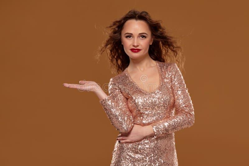 Porträt einer lächelnden Frau im goldenen Kleid, das copyspace auf der Palme auf einem braunen Hintergrund hält stockbild