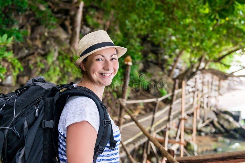 Porträt einer lächelnden glücklichen Frau mit einem Rucksackwandern stockbild
