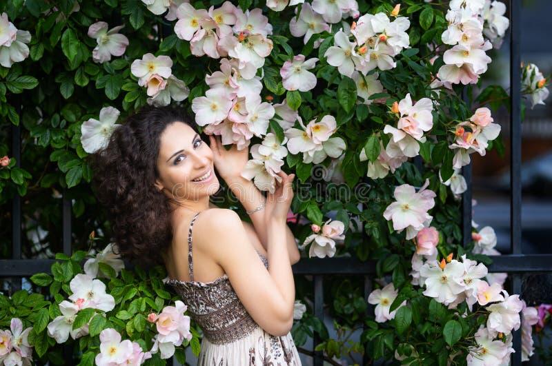 Porträt einer lächelnden jungen brunette kaukasischen Schönheit nahe Rosenbusch, Vertikale, Taille oben stockbilder