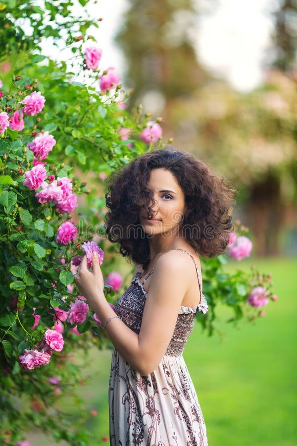 Porträt einer lächelnden jungen brunette kaukasischen Schönheit nahe Rosenbusch, Vertikale, Taille oben lizenzfreies stockbild