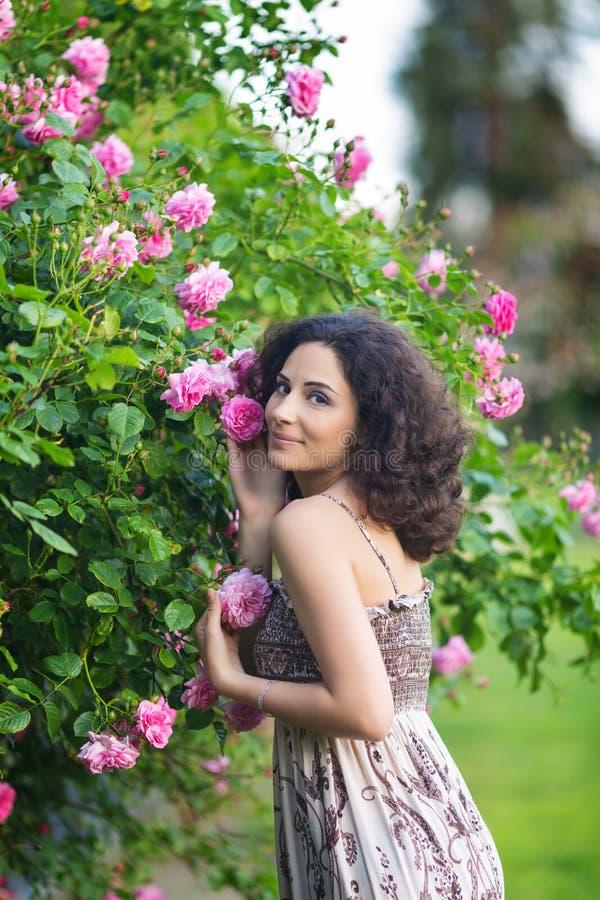 Porträt einer lächelnden jungen brunette kaukasischen Schönheit nahe Rosenbusch, Vertikale, Taille oben lizenzfreies stockfoto