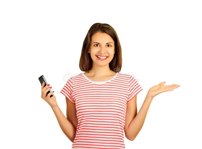 Porträt einer lächelnden jungen Frau, die ihre Arme zur Seite beim Halten eines Handys verbreitete emotionales Mädchen lokalisier stockfotografie