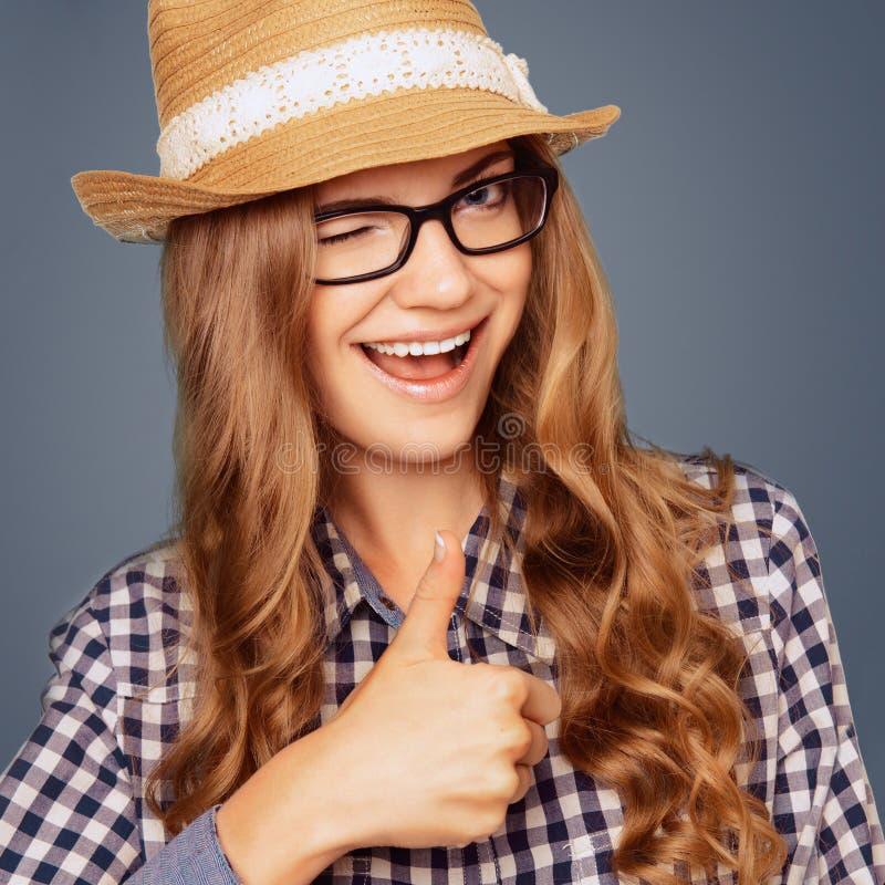 Porträt einer lächelnden jungen Frau mit zufälliger Tracht blinzelnd und stockbild