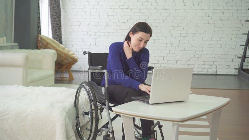 Porträt einer lächelnden jungen schönen behinderten Frau in einem Rollstuhl, zu Hause arbeitend an einem Laptop, Fernarbeit lizenzfreies stockbild
