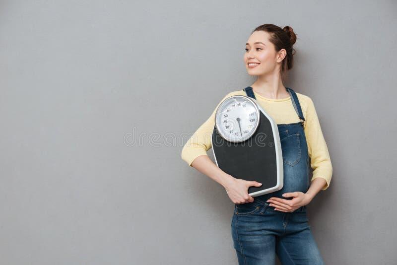 Porträt einer lächelnden jungen schwangeren Frau, die Gewichtsskalen hält stockbilder