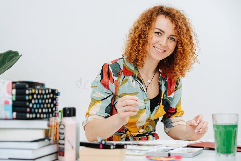 Porträt einer lächelnden Künstlerin, die hinter dem Schreibtisch sitzt, mit einer Bürste in der Hand stockbild