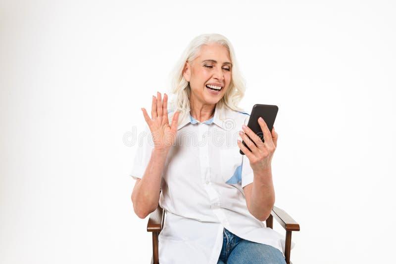 Porträt einer lächelnden reifen Frau, die auf einem Stuhl sitzt stockfotos