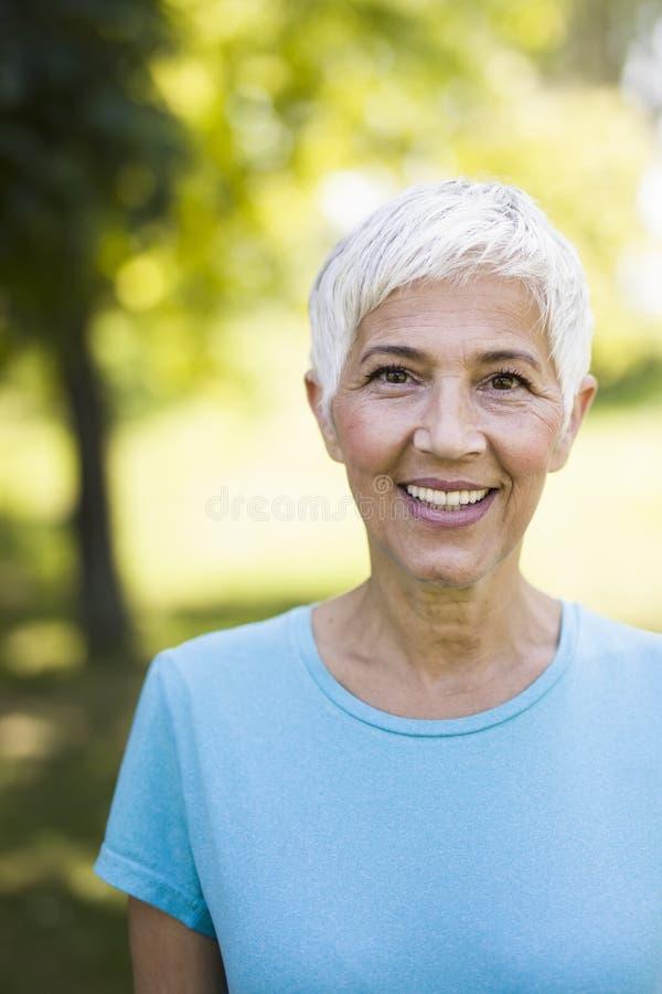 Porträt einer lächelnden sportlichen älteren Frau in einem Park stockbild