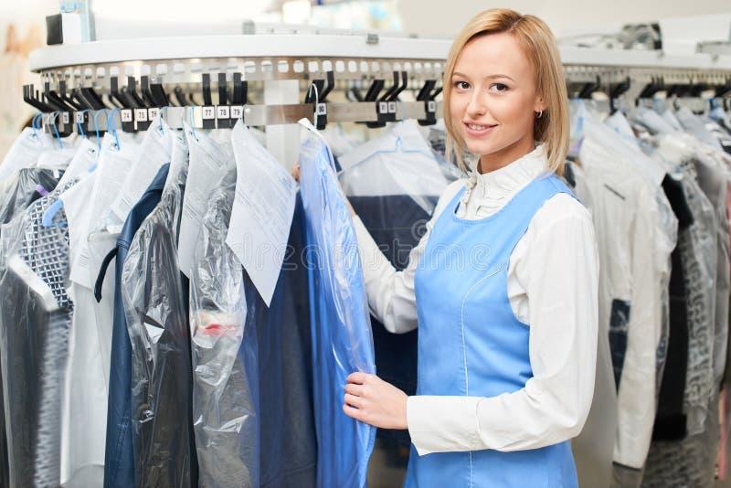 Porträt einer Mädchen Wäschereiarbeitskraft auf dem Hintergrund der Garderobenständer stockfotos