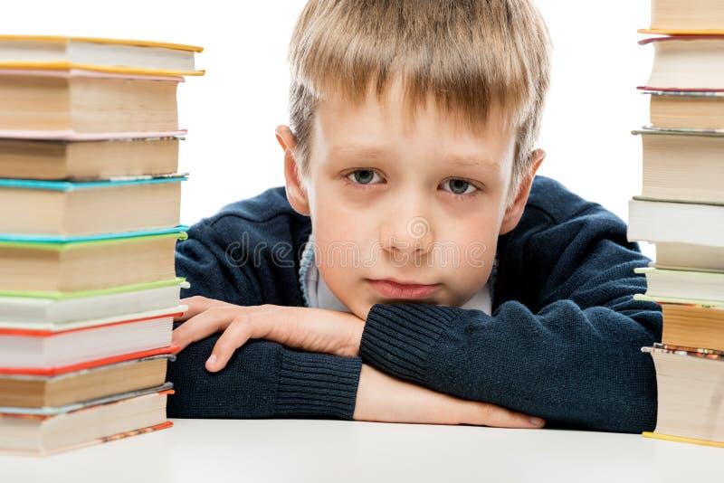 Porträt einer müden Schülernahaufnahme unter einem Stapel stockfotos